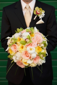 Groom holding brides bouquet